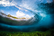Ocean Wave Barrels And Breaks Over The Shallow Coral Reef. Underwater View With The Eye Effect Of The Water