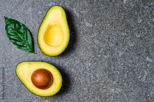 Fotografie, Obraz  Opened avocado showing seed on textured stone background.