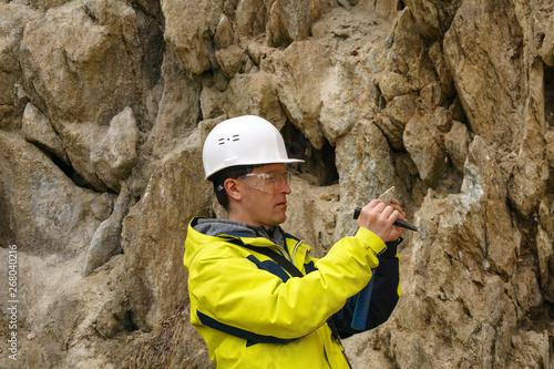 Fotografía geologist examines a sample of stone outdoor