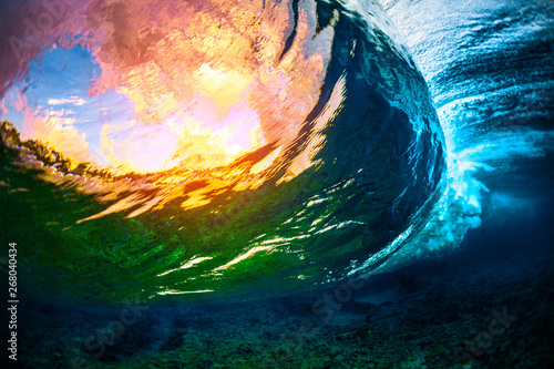 Poster Coral reefs Underwater view of the crystal clear ocean wave barreling over the coral reef with clouds and sunset sky visible through the water