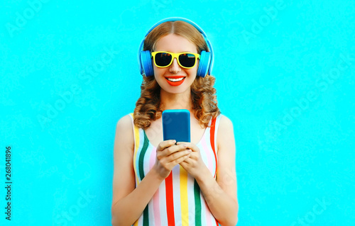 Portrait happy smiling woman holding phone listening to music in wireless headphones on colorful blue background - 268041896