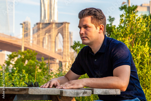 Photo Male model sitting at the table near a Brooklyn Bridge