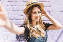 Glad Long-haired Young Woman With Hollywood Smile And Lightly Tanned Skin Making Selfie. Outdoor Close-up Portrait Of Pleased Blonde Girl In Straw Hat And Stylish Summer Dress.