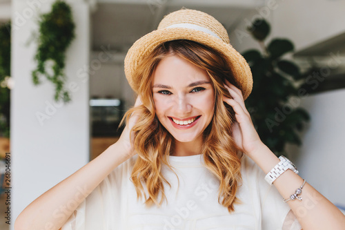 Adorable laughing girl wearing silver bracelet and white wristwatch posing on blur background with pleasure. Close-up photo of glad young woman touching curly hair and playfully smiling.