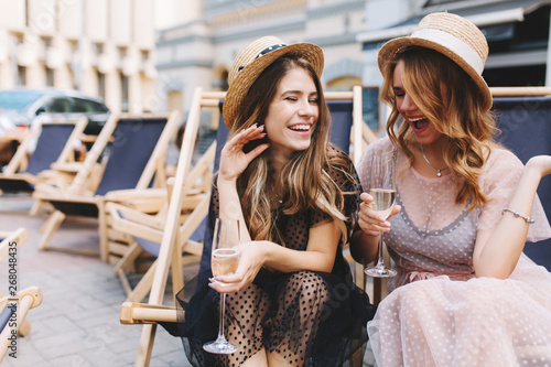 Irresistible laughing girl listening friend's joke and drink
