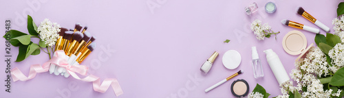 Natural woman make up cosmetics with spring white lilac bloom. Top view. Spring female decorative cosmetics on purple background. Organic cosmetic for make up banner. Cosmetic and brushes in blossom