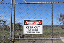 A Red, Black And White Danger, Keep Out, Authorised Personnel Only Warning Sign On A Wire Fence With A Padlocked Gate