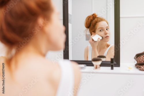 Photo  Young woman applying make-up to her face