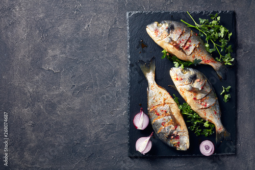 Fotografie, Obraz  three Raw dorado fish, close-up, flat lay
