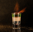 flaming cocktail with cinnamon in a shot glass on a black background, isolated