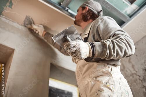 Foto auf Leinwand Texturen Workman plastering gypsum walls inside the house.