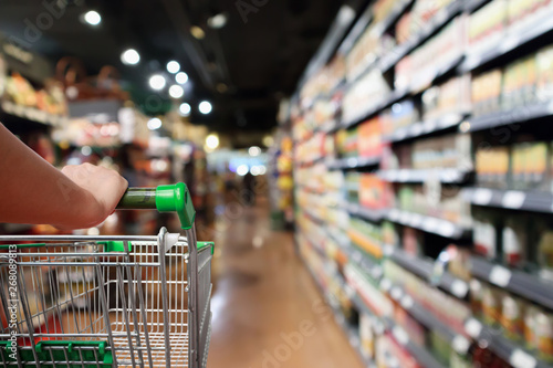 woman hand hold shopping cart with Abstract blur supermarket aisle background