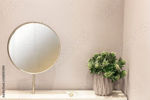 Fototapeta Round mirror frame and House plant on white dressing table