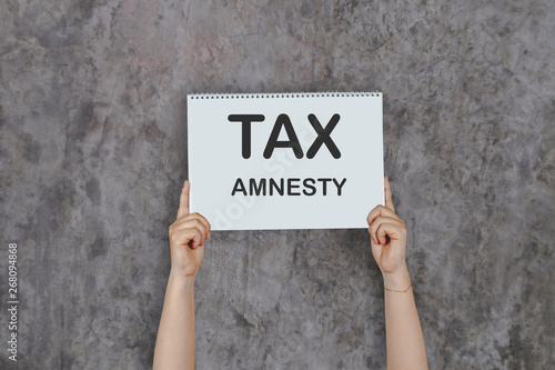 Photo Woman hands holding high a post card that says TAX AMNESTY against a old wall
