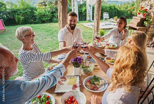 Photo  Family cheering over the dining table outdoors, celebration