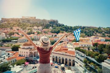 Uživanje u odmoru u Grčkoj. Mlada putujuća žena s nacionalnom grčkom zastavom uživajući u pogledu na grad Atenu i Akropolu.