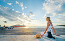 Traveling By Greece. Young Happy Woman Enjoying Beautiful Sunset On The Sea Wharf Waiting For Ferry.
