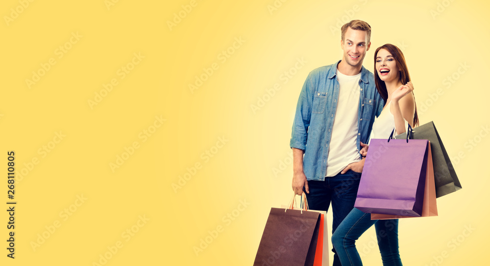 Fototapeta Photo of excited couple with shopping bags, over yellow color background
