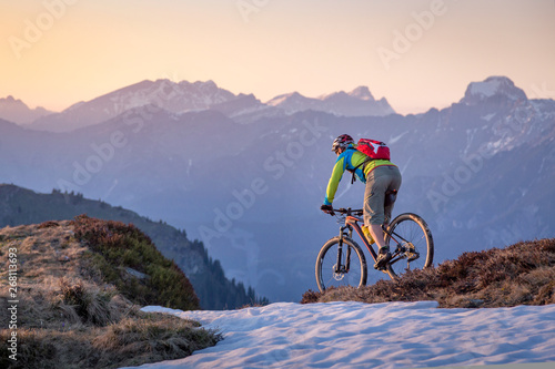 obraz lub plakat Male mountainbiker on a trail in the mountains at sunset