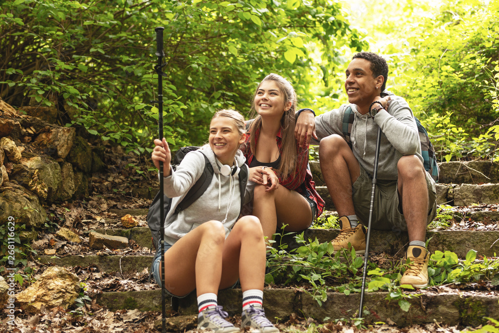 Fototapety, obrazy: Group of hikers taking a break after long walk in nature.they sitting on old path stairs.