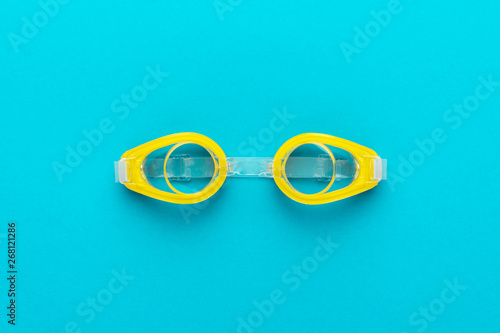 Fotomural flat lay shot of yellow swimming goggles over turquoise blue background