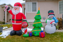 Inflatable Christmas Decorations On A Grassy Yard With Snow In Winter