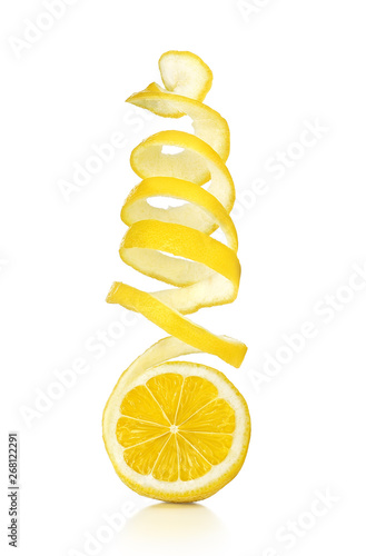 The lemon skin is twisted in a spiral with reflection on an isolated white background