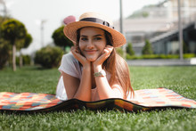 Beautiful Young Girl Is Laying On The Blanket In The Park And Smiling.