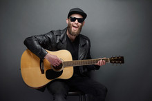 Guitar Player Singing In Music Studio. Hipster Guitar Player With Beard And Black Clothes Playing The Acoustic Guitar