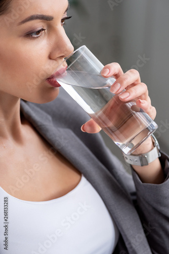 attractive woman drinking water from glass while suffering from heat on grey