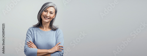 Photo  Smiling Asian senior woman with crossed arms