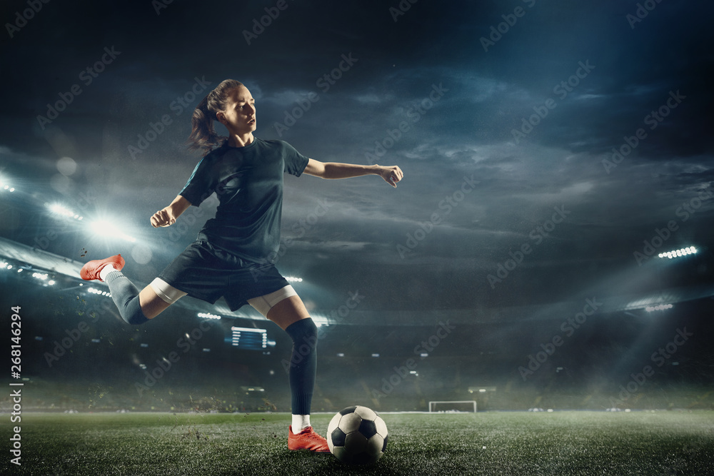 Fototapety, obrazy: Young female soccer or football player with long hair in sportwear and boots kicking ball for the goal in jump at the stadium. Concept of healthy lifestyle, professional sport, hobby, motion, movement