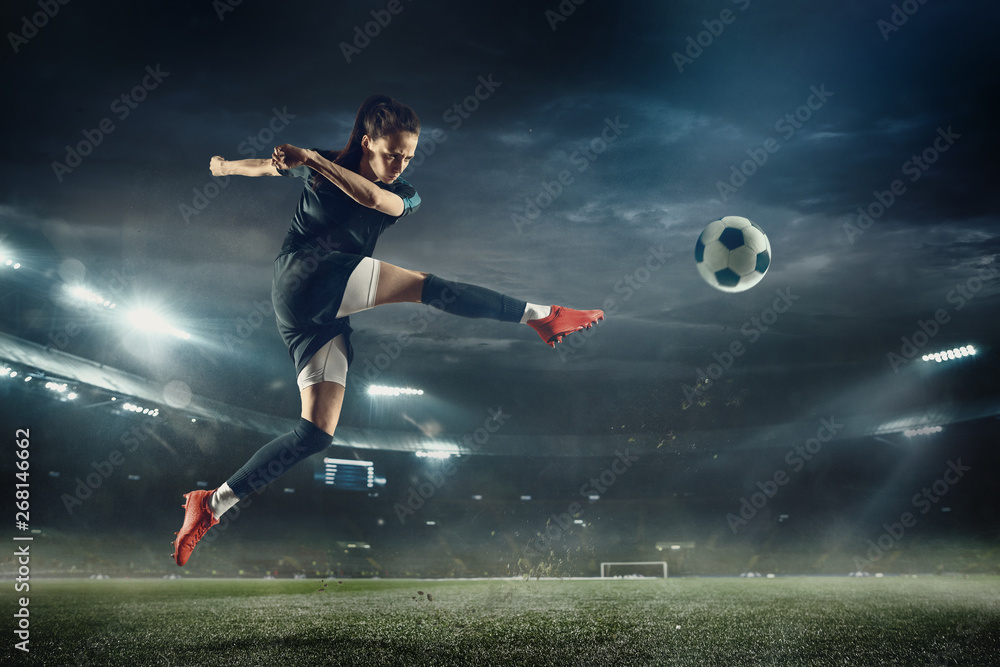 Fototapeta Young female soccer or football player with long hair in sportwear and boots kicking ball for the goal in jump at the stadium. Concept of healthy lifestyle, professional sport, hobby, motion, movement