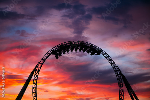 Slika na platnu Silhouette of people having fun on a roller-coaster in an amusement park at sunset