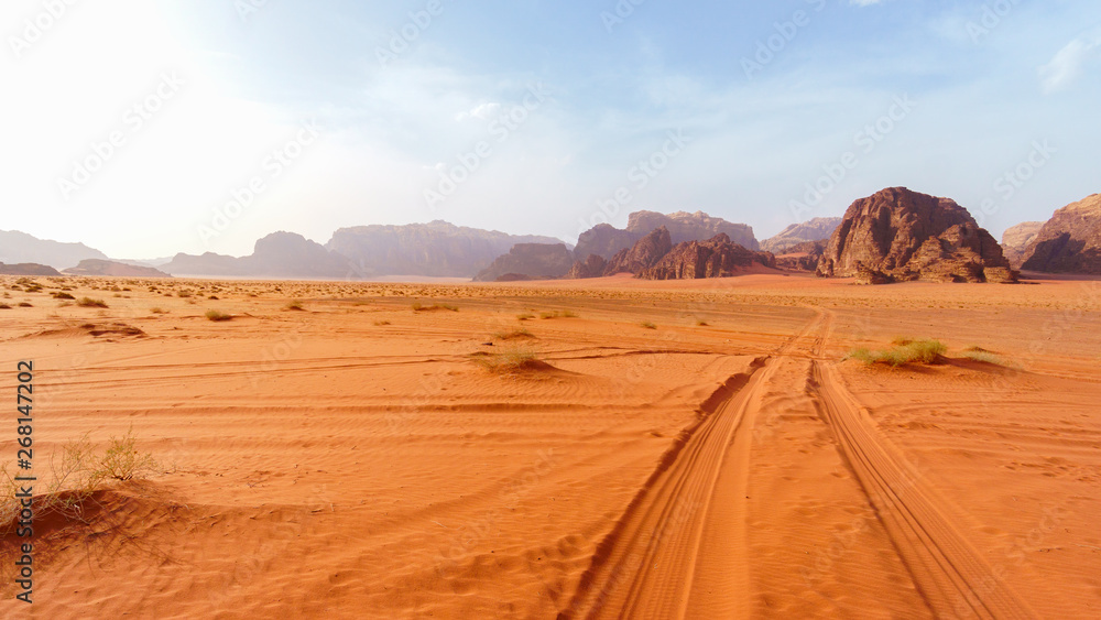 Fototapety, obrazy: Wadi Rum desert, Jordan, The Valley of the Moon. Orange sand, haze, clouds. Designation as a UNESCO World Heritage Site. National park outdoors landscape. Offroad adventures travel background.