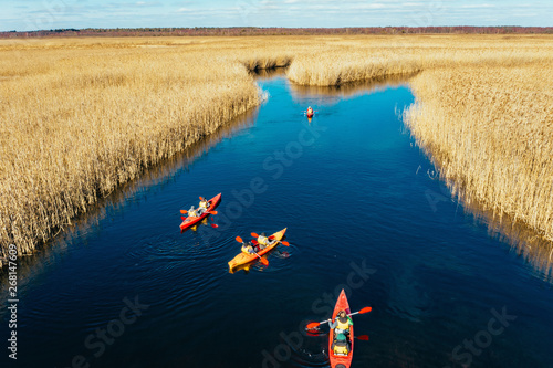 Valokuva  Group of people in kayaks among reeds on the autumn river.