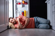 canvas print picture - exhausted man sleeping on floor in kitchen near open refrigerator