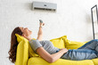 Leinwanddruck Bild - attractive young woman relaxing under air conditioner and holding remote control