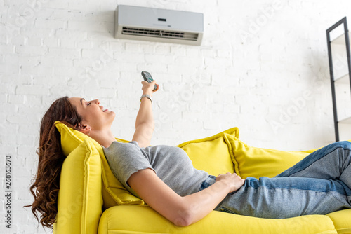 Fototapeta attractive young woman relaxing under air conditioner and holding remote control obraz