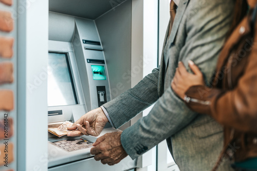 Fototapeta Senior father and his daughter using atm machine together to withdraw money