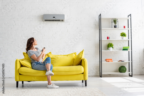 Fotomural  pretty young woman sitting on yellow sofa under air conditioner at home