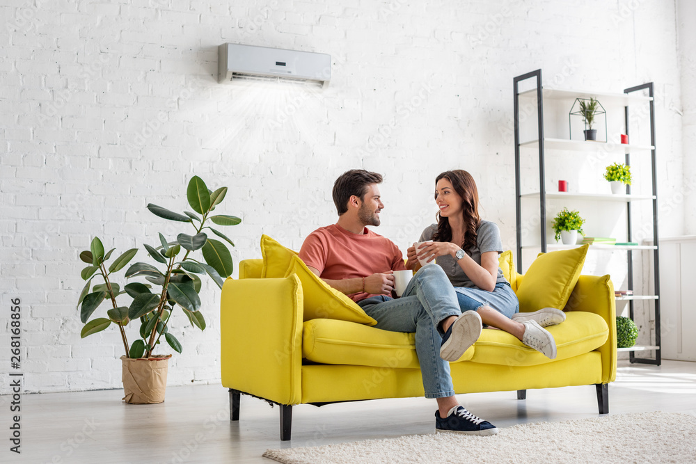 Fototapety, obrazy: happy young couple talking and holding cups while sitting on yellow sofa under air conditioner at home