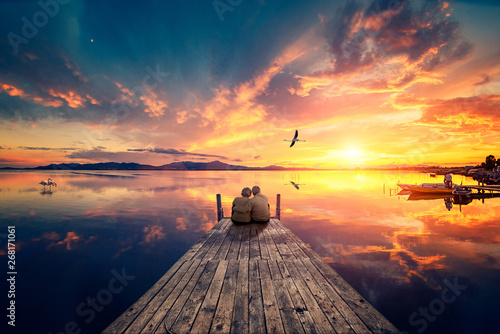Fototapeta Senior couple seated on a wooden jetty, looking a colorful sunset on the sea with a flying flamingo reflected on the calm water. obraz