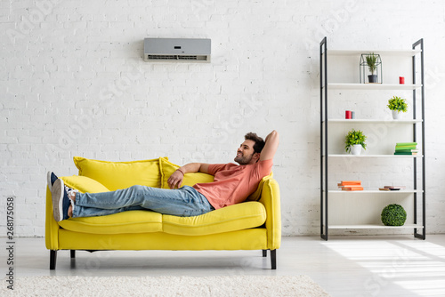 Photo  handsome smiling man lying on yellow sofa under air conditioner at home