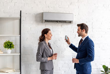 Smiling Businesspeople Talking While Standing Under Air Conditioner In Office