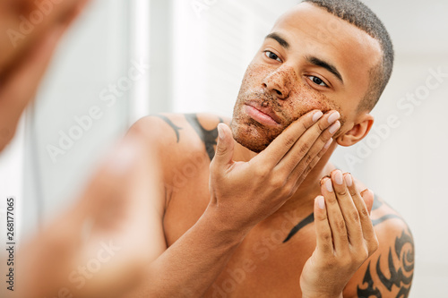 Fotografie, Obraz Handsome man applying natural scrub in front of a mirror
