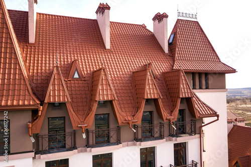 Close-up of building facade exterior with stucco wall, cast iron balcony railings, steep shingle roof and shiny windows Canvas Print