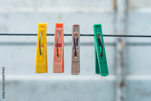 Obraz na plátně  old colored clothespins hanging on a wire for drying clothes