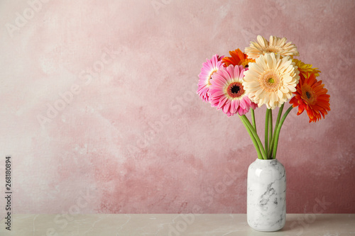 Tablou Canvas Bouquet of beautiful bright gerbera flowers in vase on marble table against color background