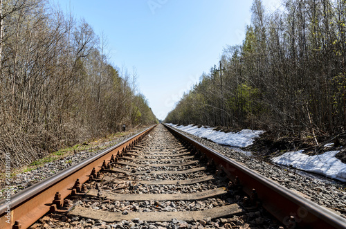the direction of a single-track railroad for old steam trains or diesel trains. rails and sleepers laid in a beautiful forest